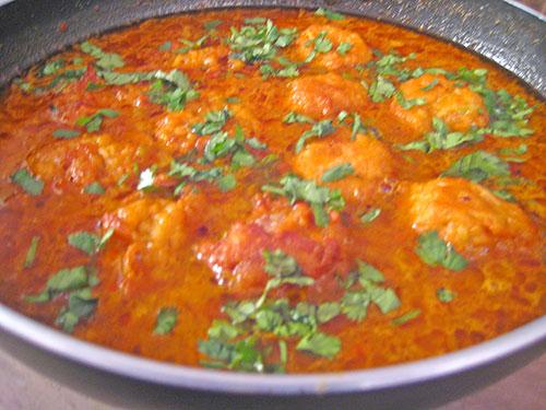 Garnishing the lauki kofta curry with fresh coriander leaves