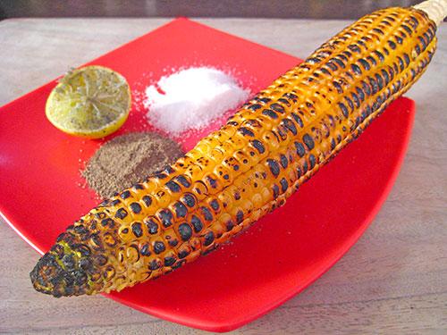Roasting of corn and apply salt, black pepper and lemon